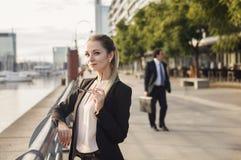 Biznesowa kobieta ono uśmiecha się outdoors z postacią behind mężczyzna fotografia royalty free