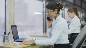 Biznesowa kobieta opowiada na telefonie komórkowym i działaniu na projekcie, biurowa atmosfera zbiory wideo