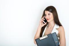 Biznesowa kobieta opowiada na telefonie przeciw białemu tłu fotografia royalty free