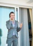 Biznesowa kobieta opowiada telefon komórkowego Zdjęcia Royalty Free