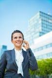 Biznesowa kobieta opowiada telefon komórkowego w nowożytnym biurowym okręgu Obrazy Stock
