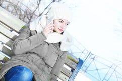 Biznesowa kobieta opowiada telefonem komórkowym na ławce Zdjęcia Stock