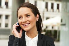 Biznesowa kobieta opowiada telefonem przeciw szklanej ścianie w ci zdjęcie royalty free