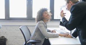 Biznesowa kobieta opowiada z szefem pracuje na komputerze w nowożytnym otwartym biurze, dwa biznesmena dyskutuje pomysł szczęśliw zbiory