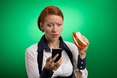 Biznesowa kobieta patrzeje telefonu komórkowego łasowania kanapkę Obraz Royalty Free
