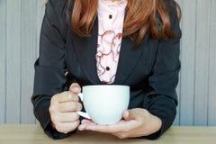 Biznesowa kobieta pije herbaty lub kawy w cukiernianym pojęciu Obraz Royalty Free