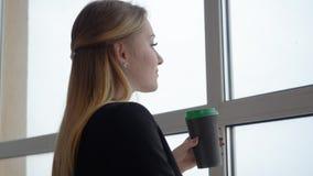 Biznesowa kobieta pije kawę od filiżanki i patrzeje okno w biurze zbiory