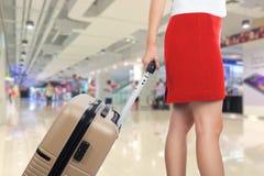 Biznesowa kobieta podróżuje walizkę w lotnisku i trzyma Zdjęcie Royalty Free