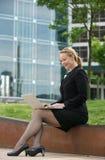 Biznesowa kobieta pracuje na laptopie na zewnątrz biura Obrazy Royalty Free