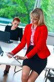 Biznesowa kobieta pracuje na pastylce z kolegą w tle Obraz Royalty Free