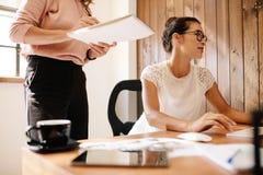 Biznesowa kobieta pracuje przy jej biurkiem z żeńskim kolegą Fotografia Royalty Free