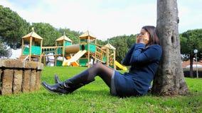 Biznesowa kobieta pracuje w parku z iPad czuciową chorobą zbiory wideo