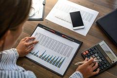 Biznesowa kobieta przy miejscem pracy przy drewnianym biuro stołem analizuje dane, rozkłady, wycenia, robi obliczenia na kalkulat Zdjęcie Stock