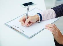 Biznesowa kobieta robi notatkom w clipboart przy biurowym miejscem pracy Zdjęcie Stock