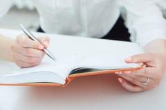 Biznesowa kobieta robi notatkom w phonebook zakończeniu przy biurowym miejscem pracy Biznesowa oferta pracy, pieniężny sukces Zdjęcia Royalty Free