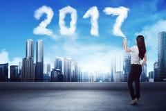 Biznesowa kobieta rozpyla biel 2017 rok chmury kształt Obrazy Stock
