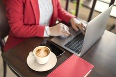 Biznesowa kobieta salowa z kawą i laptopem na drewnianym stole Zdjęcia Royalty Free