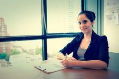 Biznesowa kobieta siedzi i pisze na przestrzeni papieru i kopii Zdjęcie Royalty Free