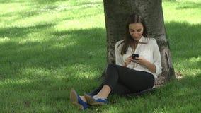 Biznesowa kobieta sprawdza jej telefonu obsiadanie pod drzewem w parku zdjęcie wideo
