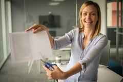 Biznesowa kobieta trzyma nożyce i rozcięcie papier sprawa szczęśliwy Obrazy Stock