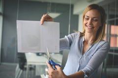 Biznesowa kobieta trzyma nożyce i rozcięcie papier sprawa szczęśliwy Zdjęcia Stock