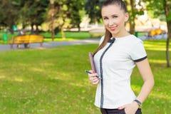 Biznesowa kobieta trzyma pióro, organizator z uśmiechem na jego twarzy pozyci w parku na słonecznym dniu i notatnik lub zdjęcia stock