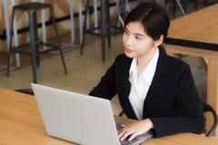 Biznesowa kobieta używa laptop sprawdza emaila, wiadomości w lub Zdjęcia Stock