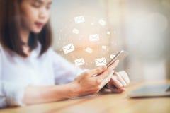 Biznesowa kobieta używa smartphone i laptop pokazujemy ikonie ogólnospołecznego emaila, pojęcie komunikacja i działanie, online zdjęcia royalty free