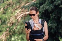 Biznesowa kobieta używa telefon z nieść jej niemowlaka outdoors w dziecko przewoźnika freelancer mama fotografia royalty free