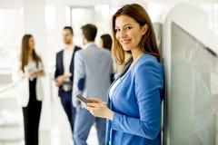 Biznesowa kobieta używa telefon podczas gdy innych biznesów ludzie Zdjęcie Stock