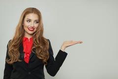 Biznesowa kobieta w czarnym kostiumu mieniu pustym otwiera rękę na białym tle zdjęcia royalty free