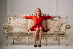 Biznesowa kobieta w czerwieni sukni na luksusowej kanapie biznesowy damy czekanie dla spotykać biznesowa kobieta relaksuje po pra Zdjęcie Royalty Free