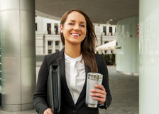 Biznesowa kobieta w kostiumu z kawiarnią i walizką na ulicznym spacerze obrazy royalty free