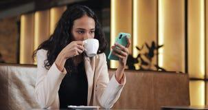 Biznesowa kobieta w menchiach nadaje się używać smartphone i pijący kawę w wygodnej kawiarni zbiory wideo