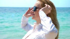 Biznesowa kobieta w okularach przeciwsłonecznych na plaży Raduje się w morzu i słońcu Rozpinał jej koszula i oddycha wewnątrz obrazy royalty free