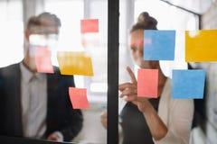 Biznesowa kobieta wskazuje przy kleistą notatką męski kolega Obraz Stock