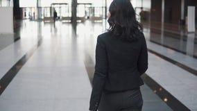 Biznesowa kobieta wychodzi przez drzwi obrotowe nowo?ytny centrum biznesu Dziewczyna w garnituru spojrzeniach przy zegarkiem zdjęcie wideo