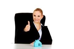 Biznesowa kobieta z błękitnego papieru domem na biurku pokazuje kciuk up Zdjęcia Royalty Free
