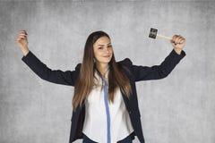 Biznesowa kobieta z dolarowymi znakami podnosi jej ręki w gescie o Fotografia Royalty Free