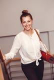 Biznesowa kobieta z niebieskimi oczami w białej bluzki koszula, czerni i dyszy mienia, przewożenia joga mata w biurze Fotografia Royalty Free