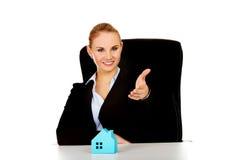 Biznesowa kobieta z otwartą ręką przygotowywającą dla uścisku dłoni i błękitnego papieru domu na biurku Obraz Stock