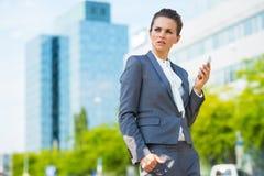 Biznesowa kobieta z telefonem komórkowym w nowożytnym biurowym okręgu Obrazy Stock