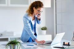 Biznesowa młoda kobieta opowiada na telefonie komórkowym podczas gdy używać jej laptop w biurze zdjęcie royalty free