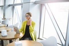 Biznesowa młoda kobieta w szkłach pracuje przy stołem w kawiarni obrazy royalty free