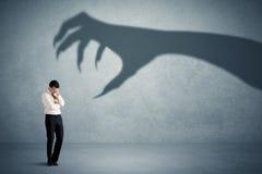 Biznesowa osoba przestraszona duży potwora pazura cienia pojęcie Zdjęcia Stock