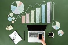 Biznesowa osoba używa cyfrowych przyrząda przy miejscem pracy z kolorowymi wykresami, ministerstwa spraw wewnętrznych pojęcie Obrazy Stock