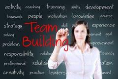 Biznesowa ręka pisze drużynowego budynku pojęciu Fotografia Stock