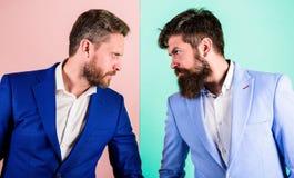 Biznesowa rywalizacja i konfrontacja Biznesmena pojawienia kurtki menchii błękita elegancki tło Spięta twarz zdjęcie royalty free