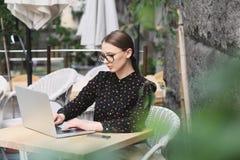 Biznesowe kobiety jest ubranym szkła, czarna koszula w kawiarni pisać na maszynie coś Obraz Stock