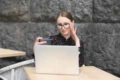 Biznesowe kobiety jest ubranym szkła, czarna koszula w kawiarni robią selfie Zdjęcie Royalty Free